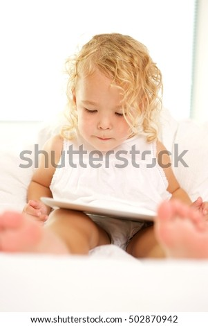 Portrait of beautiful little girl on bed using digital tablet