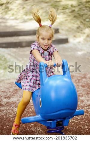 Portrait of beautiful little girl on swing in children's city park. - stock photo