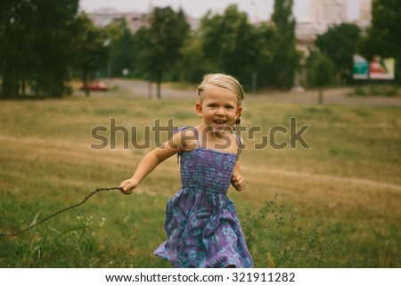 Portrait of beautiful little girl running at the park - stock photo