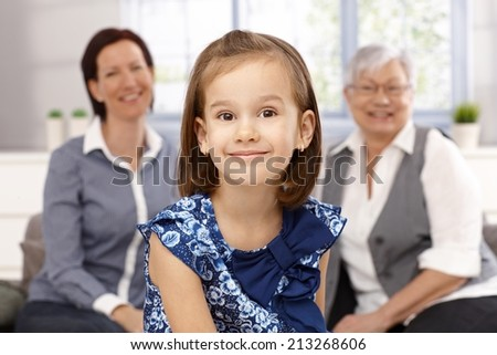 Portrait of beautiful little girl smiling happily. Mother and granny at background. - stock photo