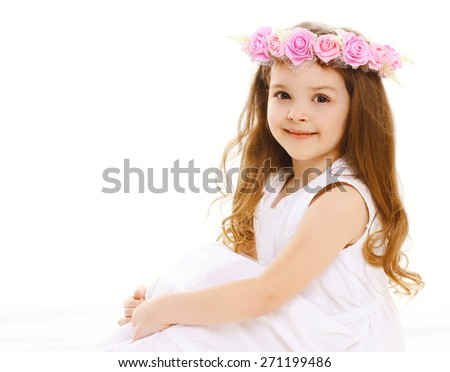 Portrait of beautiful little girl with a wreath of flowers on head