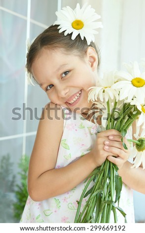 Portrait of  Beautiful little girl with dasies flowers - stock photo