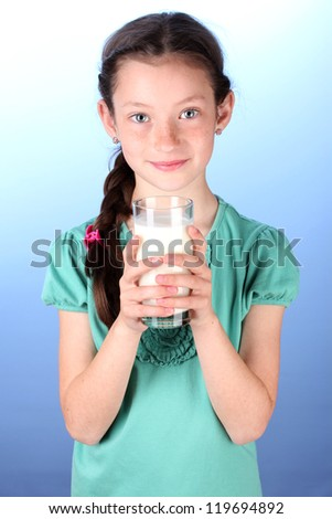 Portrait of beautiful little girl withglass of milk on blue background