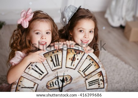 Portrait of Beautiful little girls with a big clock waiting for the new year. New year preparation - stock photo