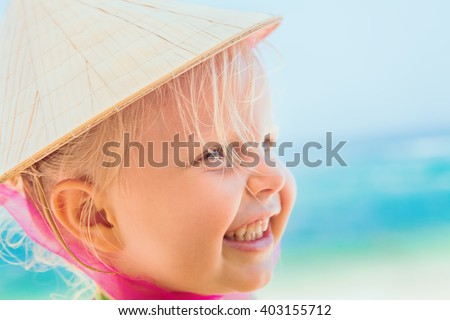 Portrait of beautiful little traveler on sunny white sand beach - happy smiling baby girl in vietnamese straw hat has fun. Active travel family lifestyle, water activity on summer vacation with child - stock photo
