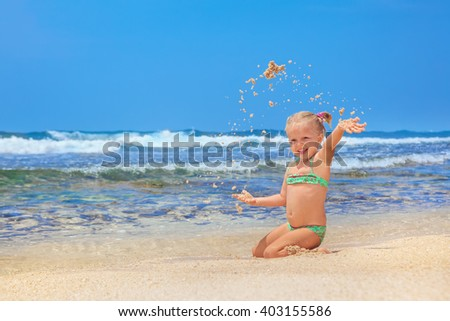 Portrait of beautiful little traveler sunbathing on sunny white sand sea beach - happy smiling baby girl has fun. Active travel family lifestyle, water activity and games on summer vacation with child - stock photo