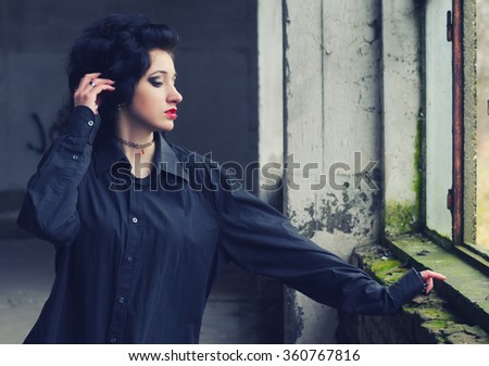 Portrait of beautiful lonely and sad goth girl in abandoned building in autumn. - stock photo