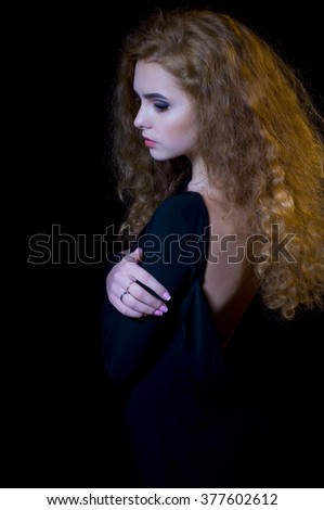 portrait of beautiful long-haired curly girl on a black background