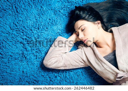 Portrait of beautiful luxury girl having fun relaxing sleeping on blue carpet copy space background - stock photo