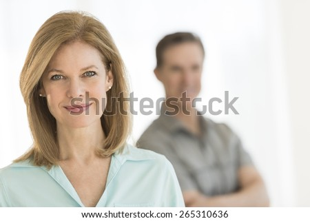 Portrait of beautiful mature woman smiling with man standing in background at home - stock photo