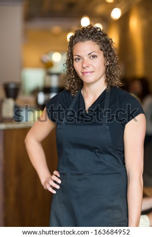 Portrait of beautiful mid adult waitress standing with hand on hip in cafe - stock photo