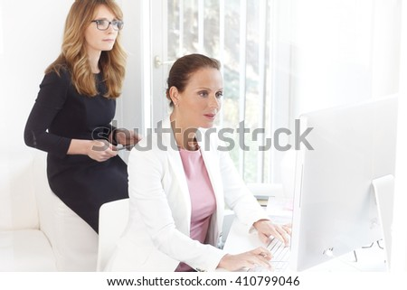 Portrait of beautiful middle age businesswomen working together on computer at office.  - stock photo