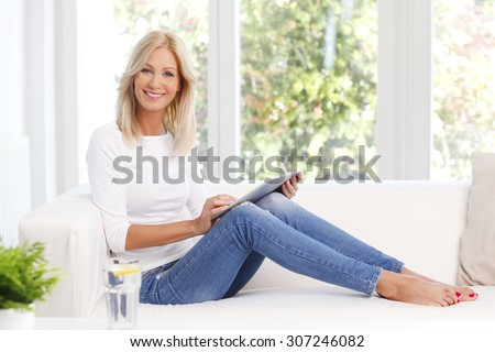 Portrait of beautiful middle age woman using digital tablet while sitting at home at sofa.  - stock photo