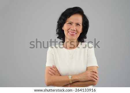 Portrait of beautiful middle-aged Vietnamese woman smiling and looking at the camera - stock photo