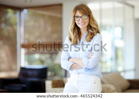 Portrait of beautiful middle aged woman sitting on sofa in her living room at home.