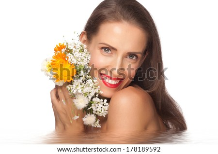 Portrait of beautiful middle aged woman with smooth healthy skin holding flowers in water