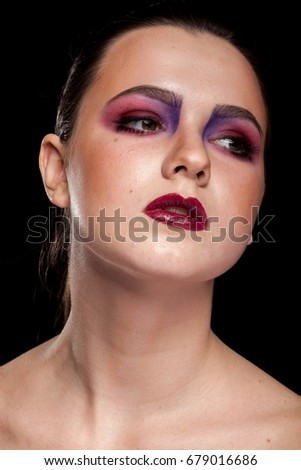 Portrait of Beautiful model woman with artistic professional make up on black background in studio photo