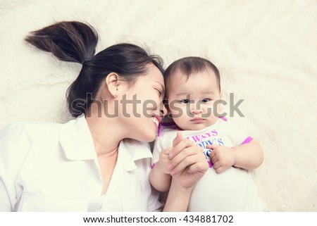 Portrait of beautiful mom playing with her 6 months old baby in bedroom, top view - stock photo