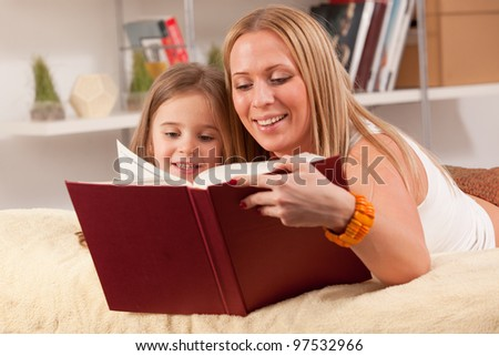 portrait of beautiful mother and daughter reading a book together - stock photo