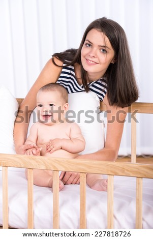 Portrait of beautiful mother and her little baby boy in the cradle at home.