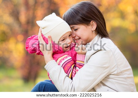 portrait of beautiful mother and kid girl outdoors in autumn park - stock photo