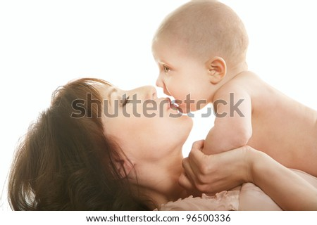 Portrait of beautiful mother kissing baby over white - stock photo