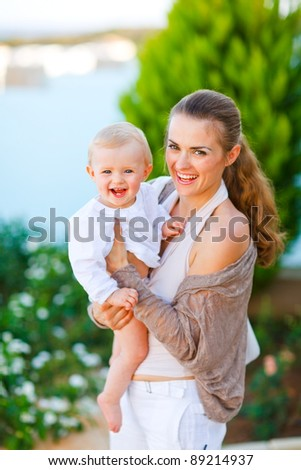 Portrait of beautiful mother with cute little baby on street - stock photo