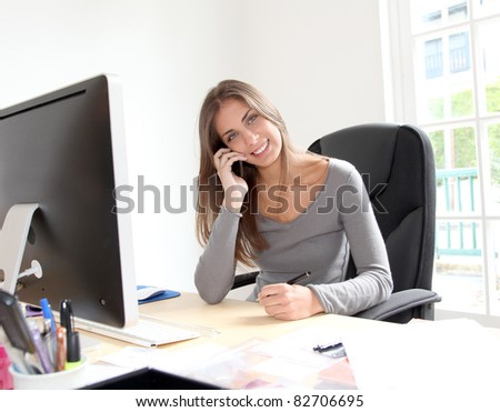 Portrait of beautiful office worker sitting at her desk - stock photo