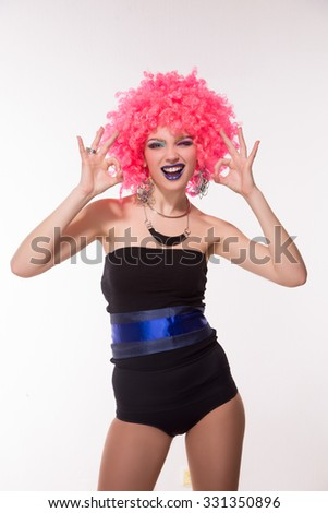 Portrait of beautiful party girl in pink wig showing okay sign with both hand. Happy lady smiling in photo studio isolated on white background.