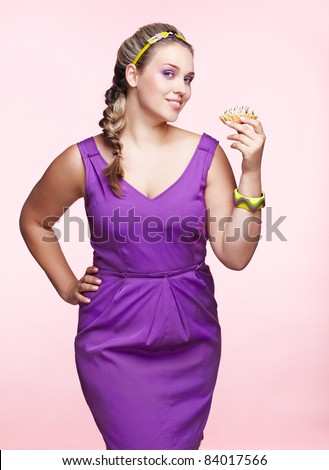 portrait of beautiful plus size curly young blond woman posing on pink with sweet pastry - stock photo