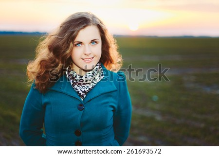 Portrait Of Beautiful Plus Size Young Woman In Blue Coat Posing In Field Meadow At Sunset Background. Spring, Outdoor Portrait - stock photo