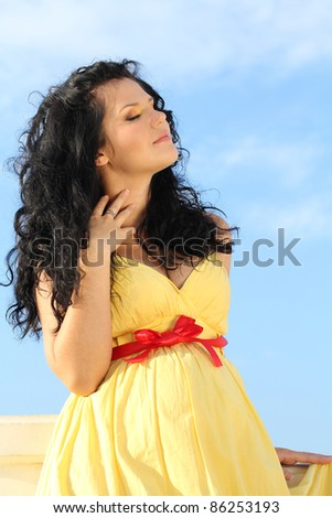 Portrait of Beautiful pregnant woman over sky - stock photo