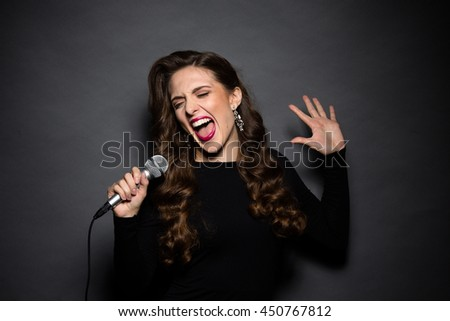 Portrait of beautiful professional musician lady singing in studio. Lady with long hair posing in black dress for camera in studio.
