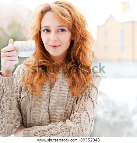 Portrait of beautiful red hair girl drinking coffee on winter background - stock photo