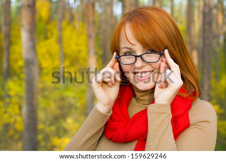 Portrait of beautiful red-haired girl in glasses outdoors