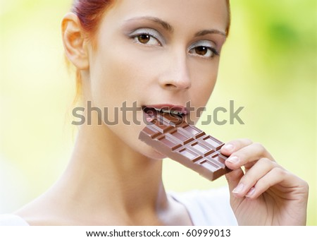 portrait of beautiful red-haired girl tasting chocolate outdoors