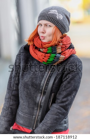 Portrait of beautiful red-haired young woman in hat and scarf looking at camera (shallow dof) - stock photo