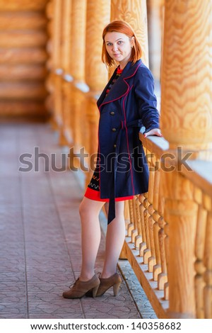 Portrait of beautiful red-haired young woman looking at camera (shallow dof) - stock photo