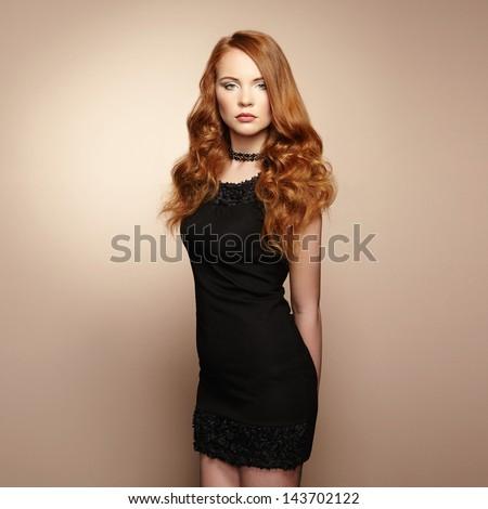 Portrait of beautiful redhead woman in black dress. Fashion photo - stock photo