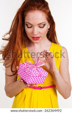 Portrait of beautiful redheaded girl with fashion makeup is holding pink gift box