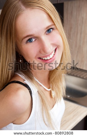 Portrait of beautiful relaxed young woman standing at the kitchen counter - Indoor - stock photo
