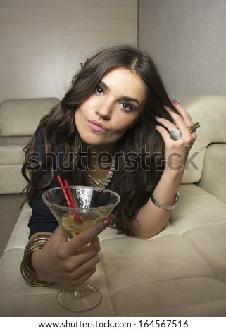 Portrait of beautiful rich woman relaxing on sofa and having a glass of martini  - stock photo