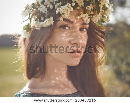 Portrait of beautiful romantic lady in a wreath of apple trees in the summer garden - stock photo