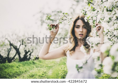 Portrait of beautiful romantic lady in apple trees blossoms - stock photo