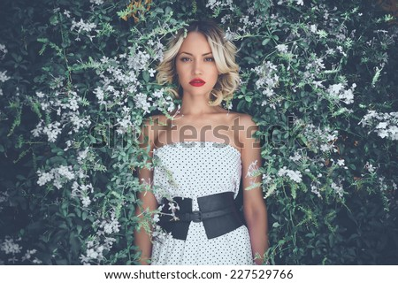 Portrait of beautiful romantic lady in the flowered garden - stock photo