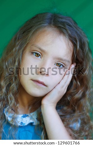Portrait of beautiful sad little girl with curly hair close up, against green background.