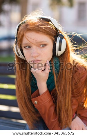 Portrait of beautiful sad pensive young woman with long red hair in headphones sitting in the park  - stock photo