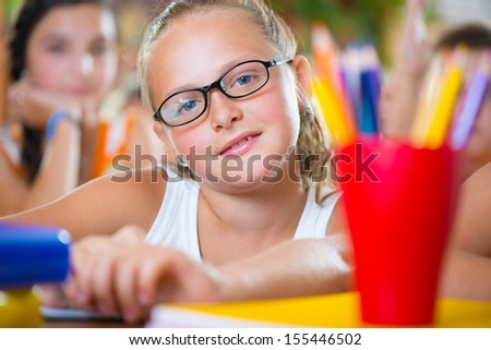 Portrait of beautiful schoolgirl girl studying in classroom at school - stock photo