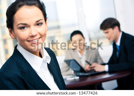 Portrait of beautiful secretary in suit looking at camera in a working environment