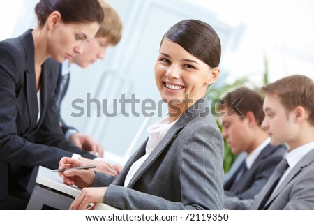 Portrait of beautiful secretary looking at camera on the background of co-workers - stock photo